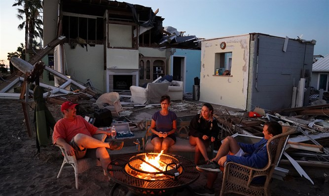 Family sits by fire, prepares to eat dinner of MREs in front of roofless house