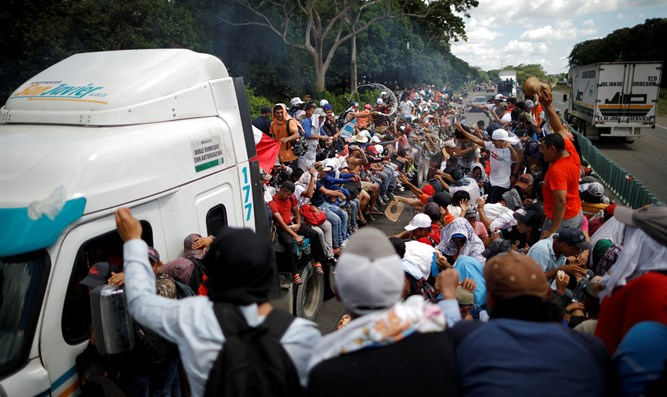 caravan of migrants trying to reach the United States hitchhike on a truck along