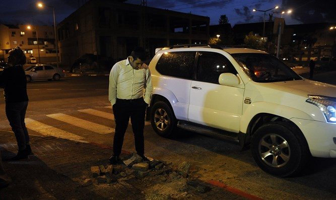 Israeli man inspects the site of Islamic Jihad rocket strike in southern town of Sderot