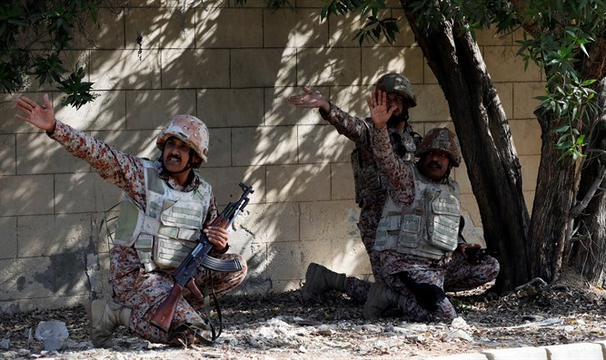 Soldiers take cover behind a wall during an attack on Chinese consulate