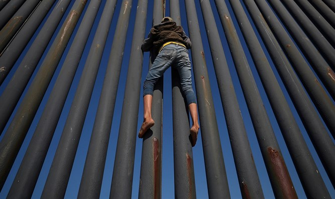 Climbing border fence between Mexico and United States in Tijuana