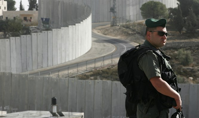 Border policeman near separation wall in Abu-Dis