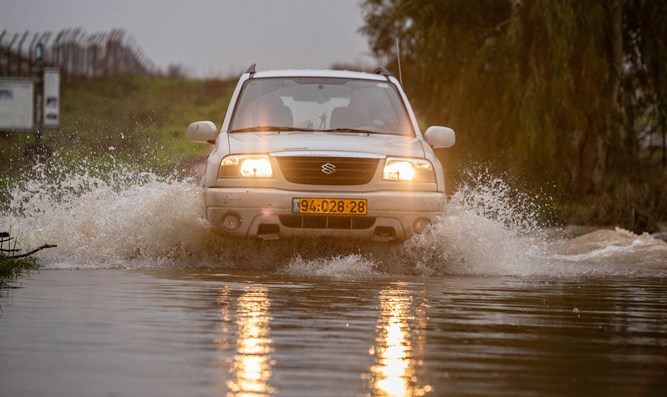 Vehicle crosses flooding stream on winter day in Golan Heights