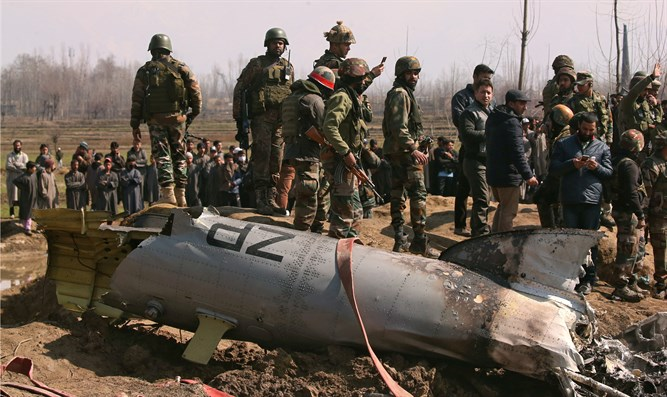 Indian soldiers stand next to the wreckage of an Indian Air Force helicopter