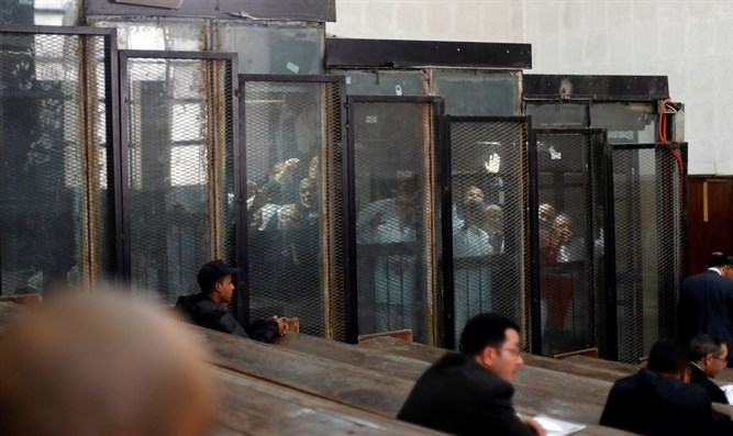Muslim Brotherhood members behind bars during court session in Cairo