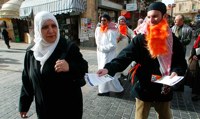 Activist dressed as Hamas lawmaker Mahmoud Abu Tir hands flyer to Arab woman