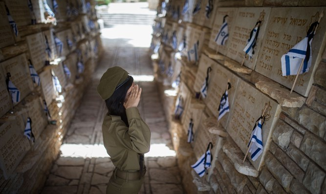 soldiers place Israeli flags on the graves of fallen soldiers in Mount Herzl