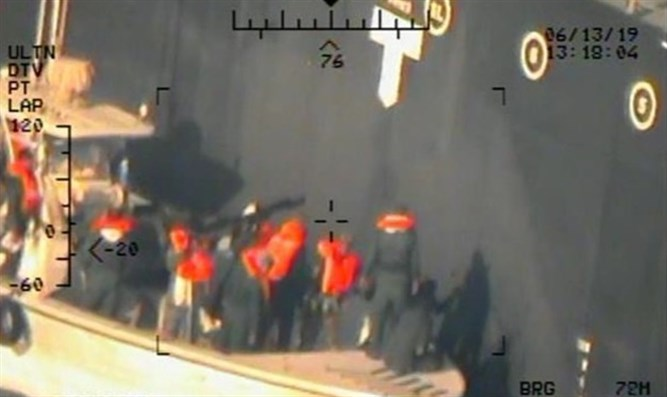 US military image of Iranian personnel removing unexploded mine from vessel