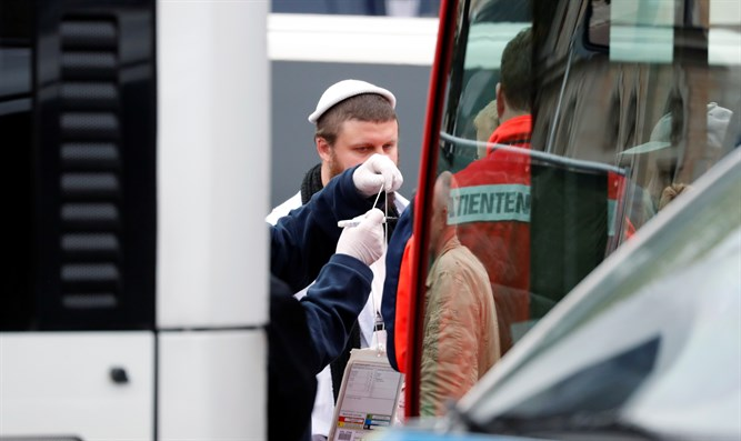 Jewish man is escorted from from the site of a shooting in Halle