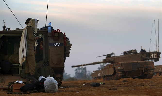 Israeli soldier prays by an APC at the Gaza border