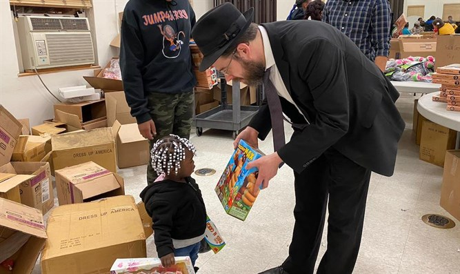 Rabbi Moshe Schapiro shows a toy to a child during the charity drive in Jersey City
