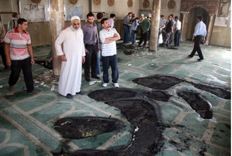 Muslims inspect partially burnt mosque