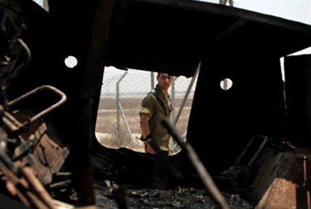An Israeli soldier walks past a burned Egypti