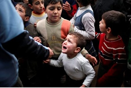 A Syrian child refugee cries in a queue waiti