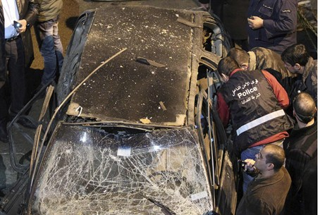 Security policemen inspect a damaged car in t