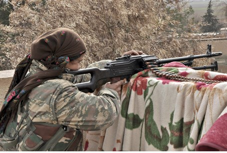 A female Kurdish YPG fighter takes aim at the