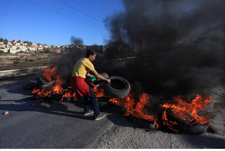 Palestinian Arabs burn tires, block Israeli r