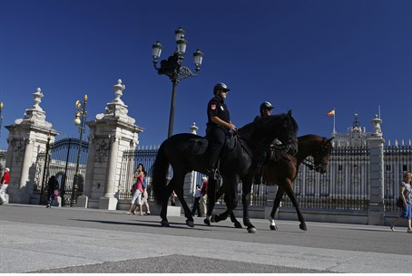Mounted police officers patrol outside the Royal Palace in Madrid