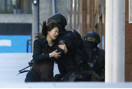 A hostage runs towards a police officer outside Lindt cafe, where other hostages are being