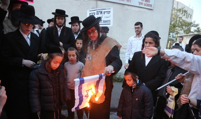 Neturei Karta members burn Israeli flag