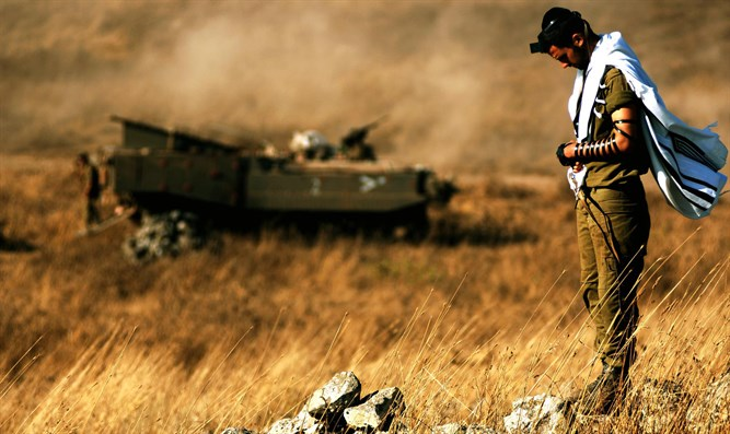 Religious IDF soldier prays near his APC