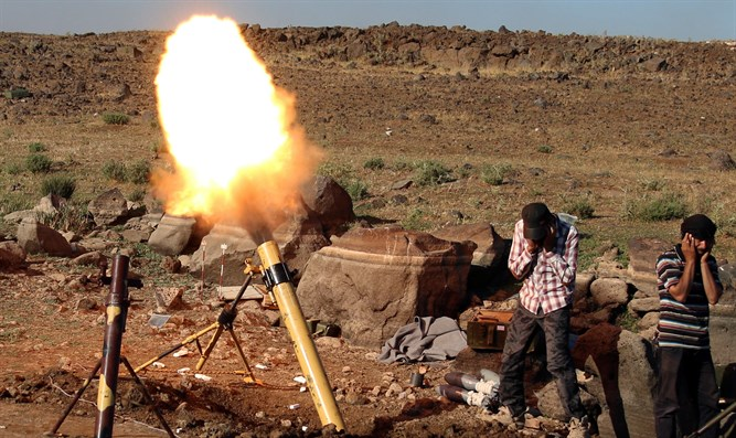 Rebel fighters fire mortar shells towards forces loyal to Syria's President Bashar al-Assa