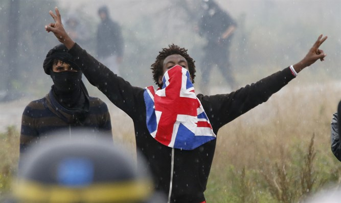 "Migrant reacts near French riot police during protest near area known as the ""jungle"""