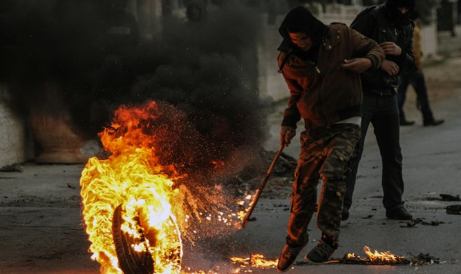 Arab rioter rolls burning tire with a stick