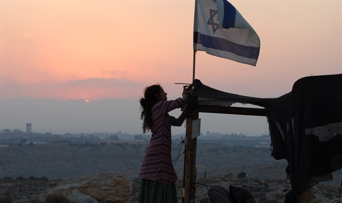 Jewish girl raises Israeli flag at the Israeli village of Avnei Hefetz, Samaria