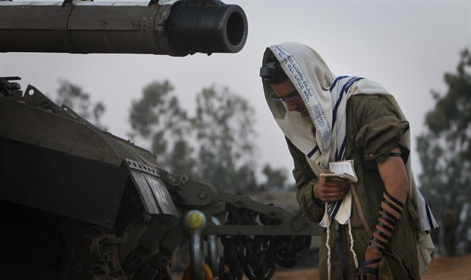 Armored Corps soldier prays before operation near Gaza