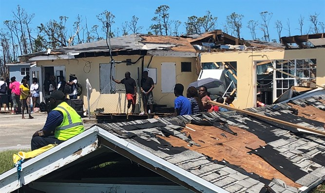 Survivors of Hurricane Dorian use destroyed roof as a bench in Abaco, Bahamas.