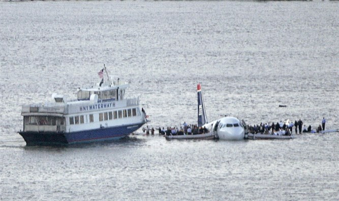 Passengers stand on the wings of a U.S. Airways plane as a ferry pulls up to it