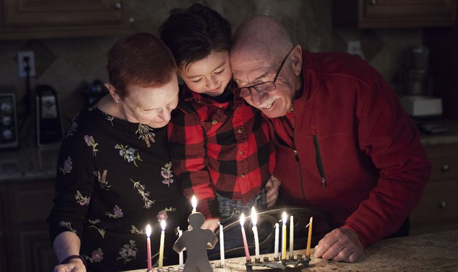 Granparents and grandson lighting Hanukkah Candles