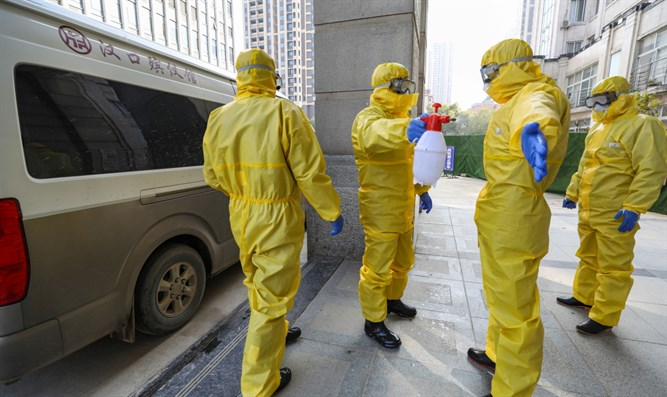 Staff at funeral parlor wear protective suits to protect against the coronavirus in Wuhan